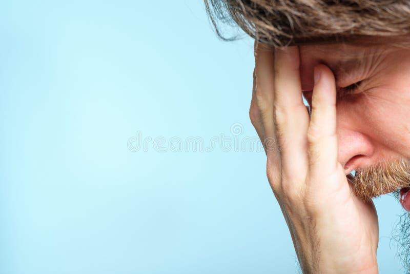 Van de de spanningsmens van de hoofdpijnmoeheid emotioneel de holdingshoofd stock afbeeldingen
