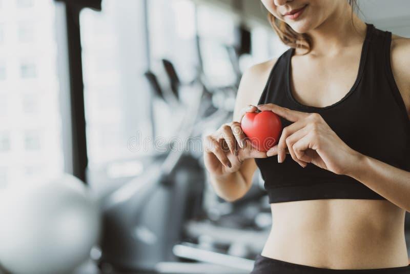 Van de de sportvrouw van het gezondheidszorg rode hart de trainingoefening bij gymnastiekfitness gezonde levensstijl royalty-vrije stock afbeeldingen
