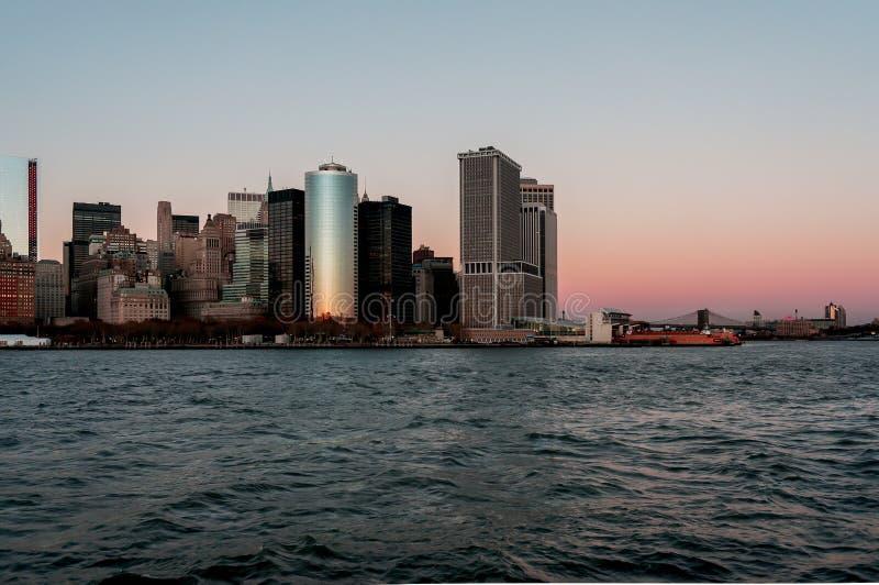 Van de de stadshorizon van New York de zonsondergangmening van de boot aan Ellis Island royalty-vrije stock fotografie