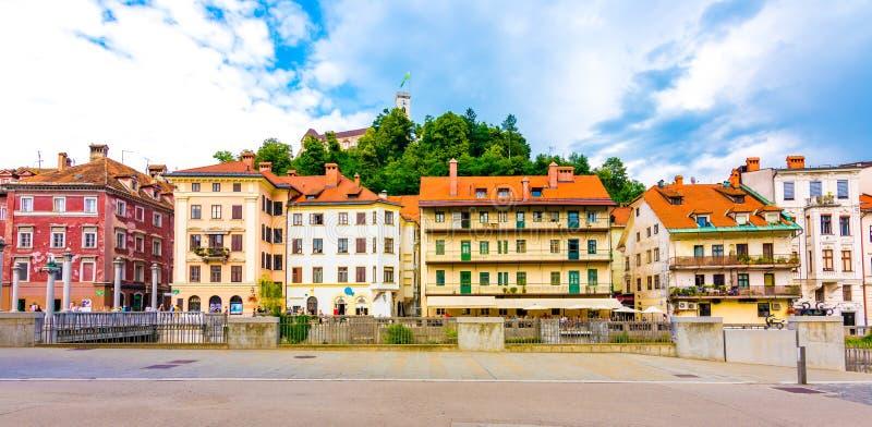 Van de de stadsstraat van Ljubljana het panoramamening Oude gebouwen en historische architectuur Het oude kasteel op de heuvel in royalty-vrije stock foto