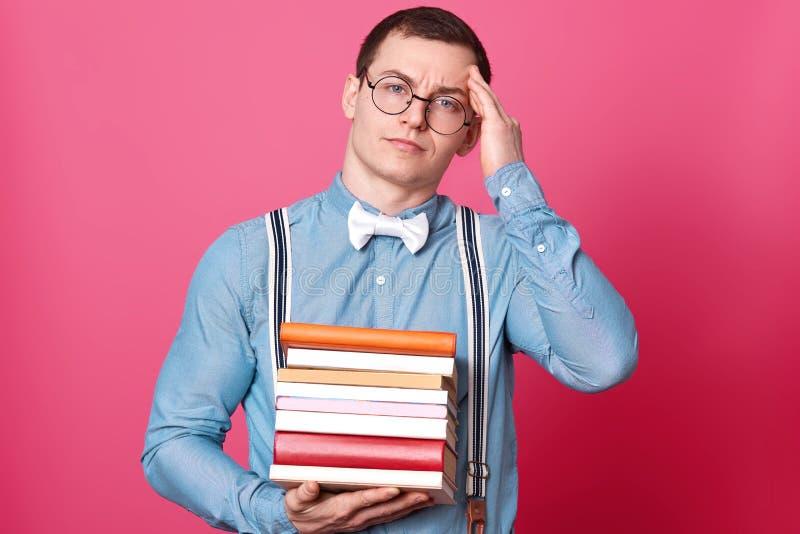 Van de de studentenmens van beeldfo houdt de jonge de holdingsstapel van boeken en het hebben van hoofdpijn, hand op hoofd, stelt stock fotografie