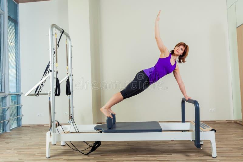 Van de trainingoefeningen van de Pilateshervormer de vrouwenbrunette bij gymnastiek binnen stock foto