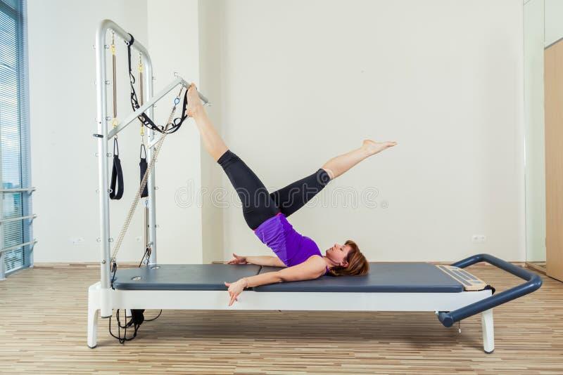 Van de trainingoefeningen van de Pilateshervormer de vrouwenbrunette bij gymnastiek binnen stock afbeelding