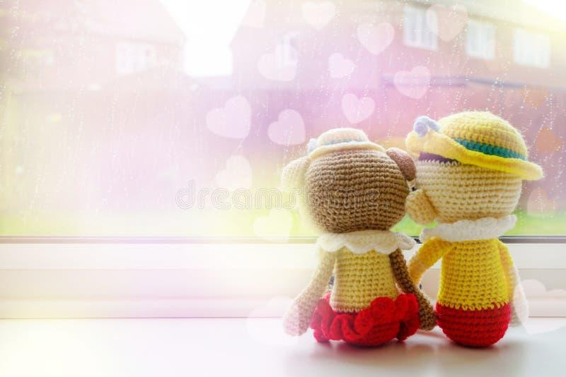 Van de twee breiende poppenmeisje en jongen zitting naast het venster, Liefdekaart stock foto's