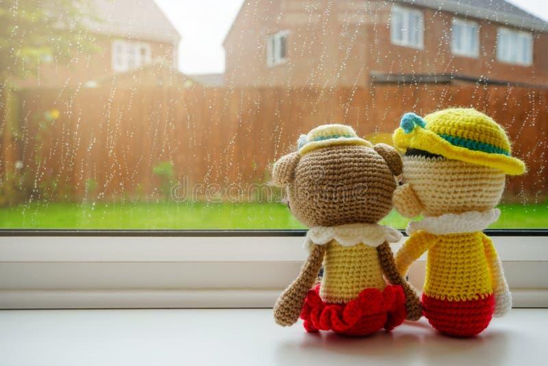 Van de twee de breiende poppenmeisje en jongen zitting van de holdingshand naast het venster stock afbeelding