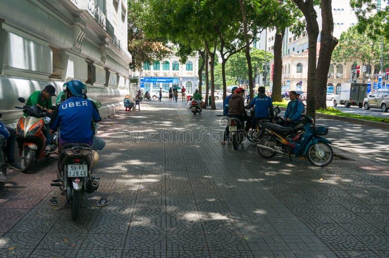 Van de Uberautoped en motorfiets bestuurders die rust op straten van Ho Chi Minh City, Vietnam hebben royalty-vrije stock fotografie