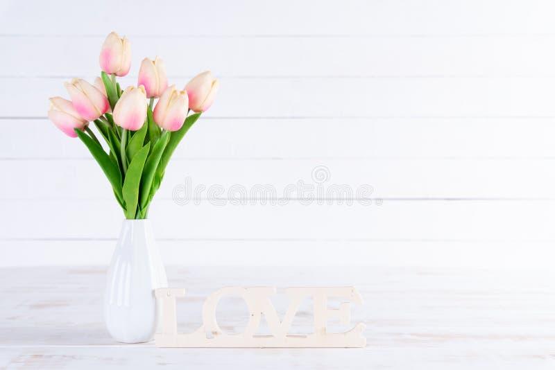 Van de valentijnskaartendag en liefde concept Roze tulpen in vaas met Houten brieven die die woordliefde vormen op witte houten a royalty-vrije stock foto's
