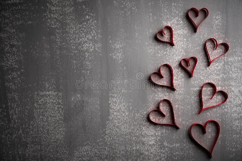 Van de valentijnskaartendag en liefde concept Velen behangen rode harten op grijze houten achtergrond stock afbeeldingen