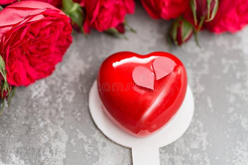 Van de valentijnskaartendag of verjaardag groetkaart Cake in de vorm van een rood hart Rood rozen en dessert op uitstekende houte royalty-vrije stock fotografie