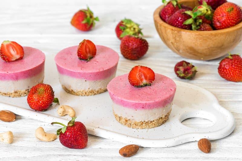 Van de veganist ruwe aardbei en banaan cakes met verse bessen en noten Gezond voedsel royalty-vrije stock foto's