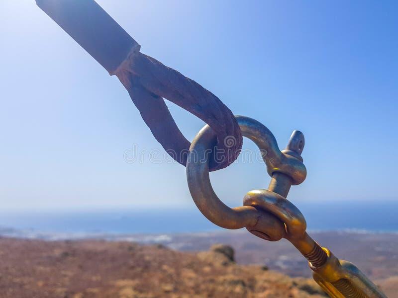 Van de veiligheidsslot en draad de lijnkabels verbonden in de voorgrond met elkaar met hemel en overzeese bodems Beeld in Lanzaro stock fotografie