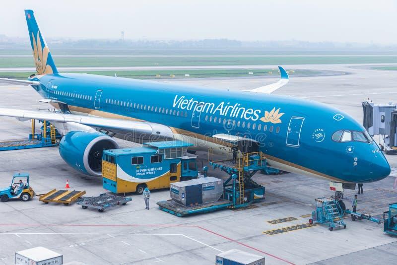 Van de de vliegtuigenlading van Vietnam Airlines VN de luchtvrachtcontainers vóór vlucht bij de internationale luchthaven van Noi royalty-vrije stock afbeelding