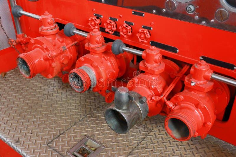 Van de de vrachtwagenslang van de brandweermanbrand de tapkranen op een rij rood en zilver stock afbeeldingen