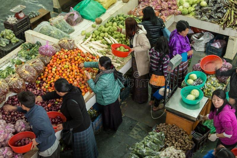 Van de vrouwen het kopen en verkoper kruidenierswinkels in een markt in Thimphu, de hoofdstad van Bhutan royalty-vrije stock foto