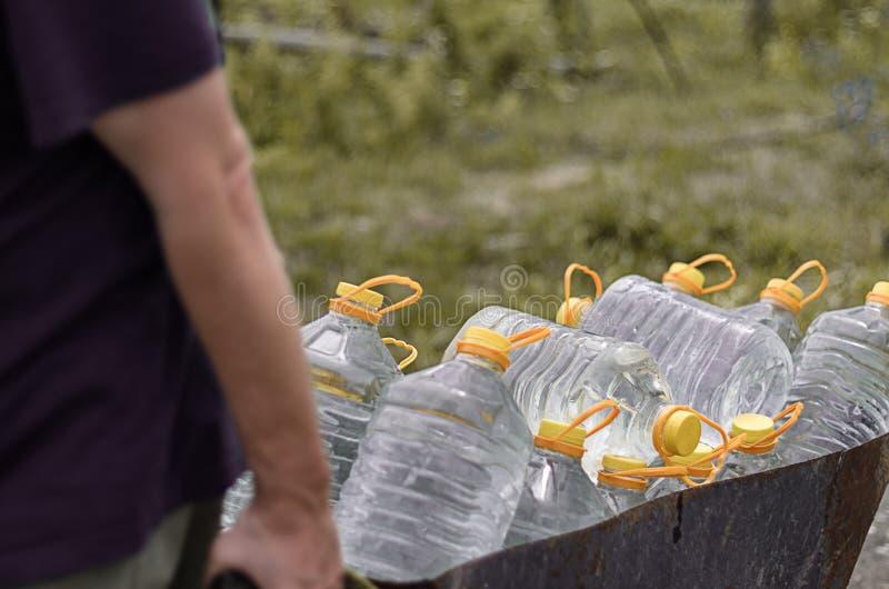 Van de wateraanbodtekort en klimaatverandering bedreigingen Het witte mannetje trekt een kar van plastic die flessen met schoon w stock foto's