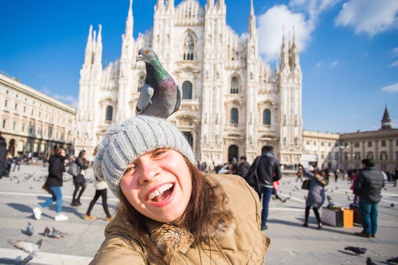 Van van de winterreis, vakanties en vogels concept - Jonge grappige vrouw die selfie met duiven dichtbij Milan Cathedral Duomo-Di stock foto's