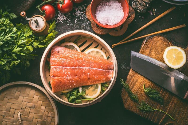 Van de zalmfilet en citroen plakken in bamboestoomboot op donkere rustieke keukenlijst met ingrediënten en hulpmiddelen Het gezon royalty-vrije stock fotografie