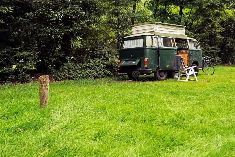 Van di campeggio d'annata sul prato in foresta fotografia stock libera da diritti