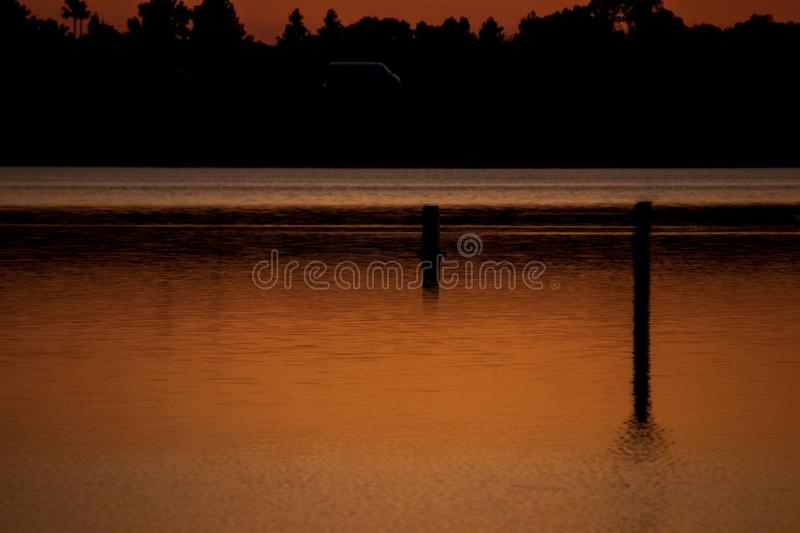 Van driving on road behind bay of water where golden sunset is reflected with silhouette of trees in background. California stock image