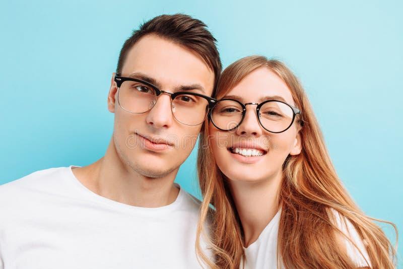 Van een jong gelukkig paar, die glazen, de mens en vrouw, het glimlachen dragen, die de camera onderzoeken, tegen een blauwe acht stock foto