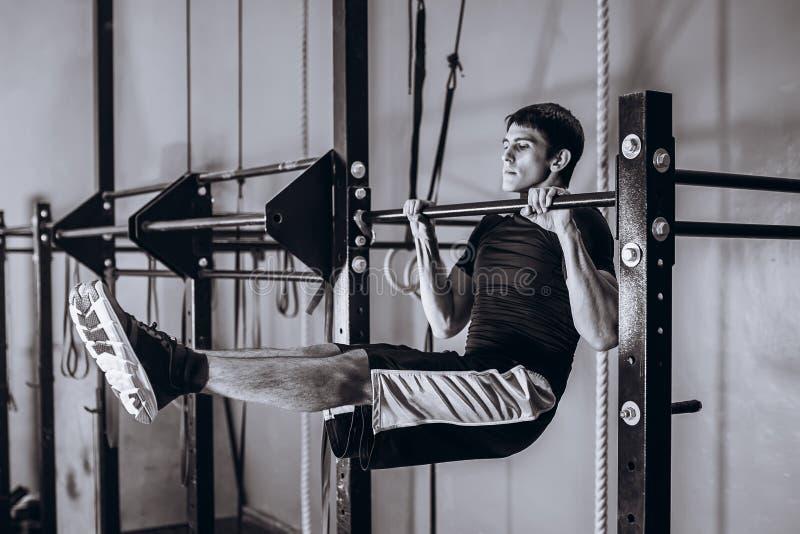 Van gemiddelde lengte van het sterke mens doen trek op een dwarsligger uit - rekstok Hangende Abs stock afbeeldingen