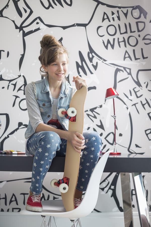 Van gemiddelde lengte van meisje met skateboardzitting op studielijst thuis stock afbeelding