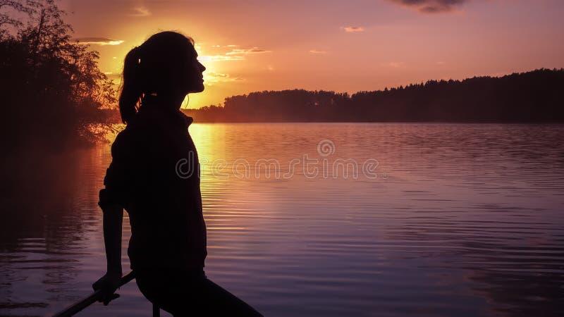 Van het achtergrond silhouetmeisje zon Meisje die dichtbij water zich in openlucht bevinden Gouden zonsondergangmeer Jonge vrouw  stock foto