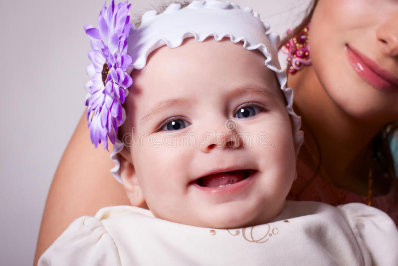 6 van het babymaanden meisje die met een bloem op haar hoofd glimlachen stock afbeelding