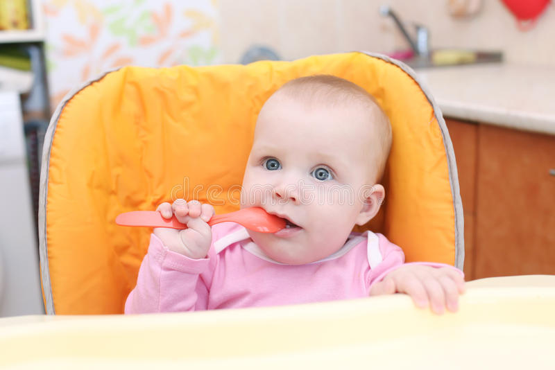 7 van het babymaanden meisje op highchair in keuken stock afbeelding