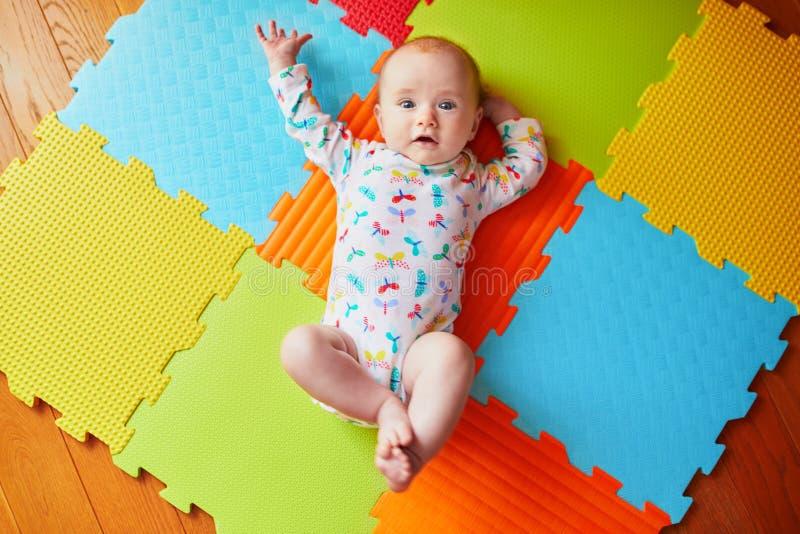 4 van het babymaanden oud meisje die op kleurrijke spelmat liggen royalty-vrije stock afbeelding