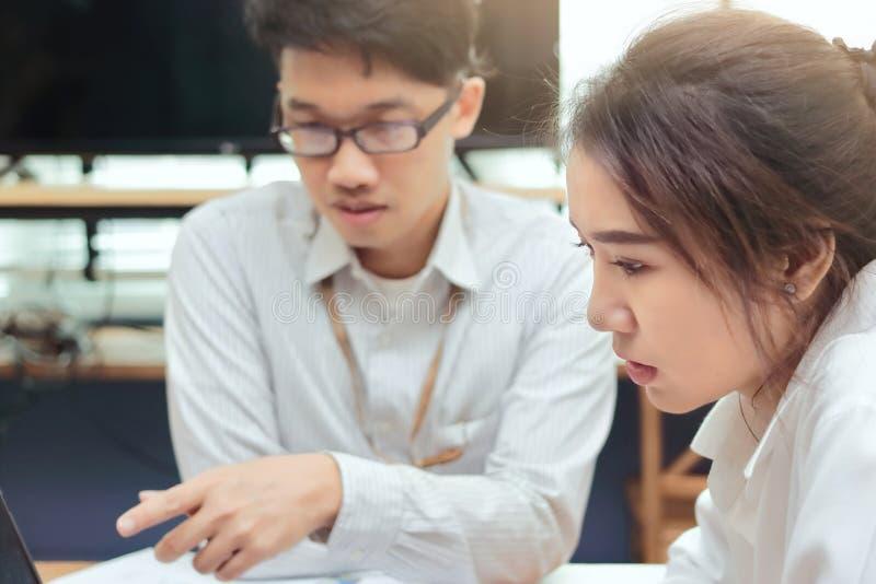 Van het bedrijfs groepswerk concept Twee jonge Aziatische werknemersbrainstorming samen in modern bureau Van het bedrijfs teamwer stock fotografie