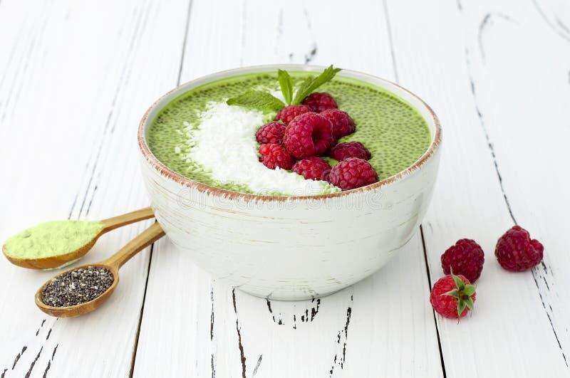 Van het chiazaad van de Matcha groene thee de puddingskom, veganistdessert met framboos en kokosmelk De lucht, hoogste vlakke men stock afbeeldingen
