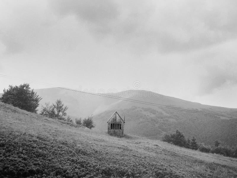 Van het de aardlandschap van bergenheuvels de enige hut stock foto