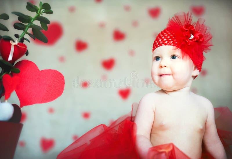 Van het de Dagconcept van Valentine het exemplaarruimte Weinig baby met kussen van lippenstift Een meisje met een rood hart Heili stock foto