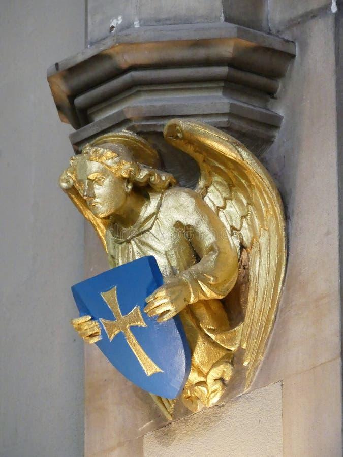 Van het de engelenbeeldhouwwerk van de kerkmuur gouden de holdingsschild en neer het kijken royalty-vrije stock foto's