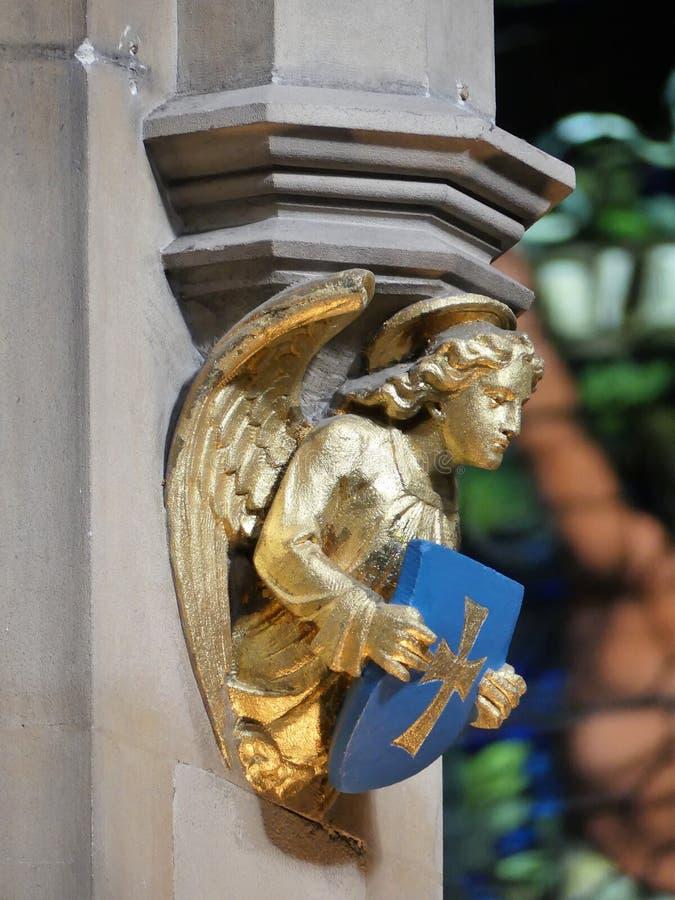 Van het de engelenbeeldhouwwerk van de kerkmuur gouden de holdingsschild en neer het kijken royalty-vrije stock fotografie