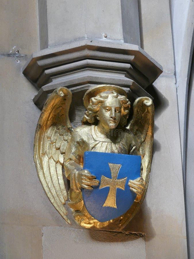 Van het de engelenbeeldhouwwerk van de kerkmuur gouden de holdingsschild en neer het kijken stock afbeeldingen