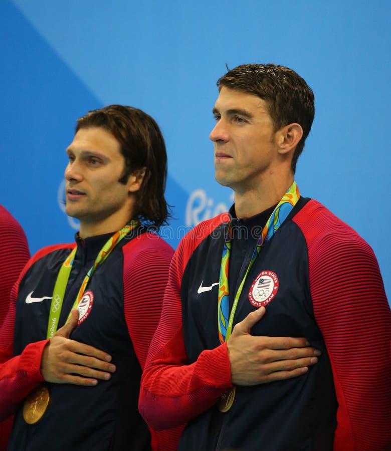 Van het de hutspotrelais van Mensen 4x100m van de V.S. het team Cory Miller (l) en Michael Phelps viert overwinning in Rio 2016 O stock afbeeldingen