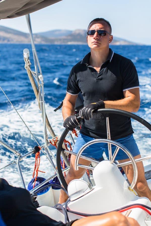 Van het de jonge ossenwiel van de jonge mensenkapitein varende het jachtboot stock afbeelding