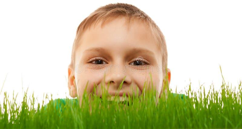 Van het de jongensgezicht van het kindjonge geitje van de de close-up isoleerde het gelukkige glimlach groene gras wit stock foto