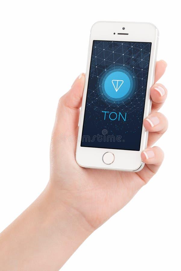 Van het de TONembleem van het telegram Open Netwerk het Witboek op iPhonevertoning in vrouwelijke hand stock foto