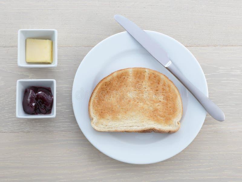 Van het de toostmes van de ontbijtplaat boter de jamgelei op houten lijst royalty-vrije stock afbeelding