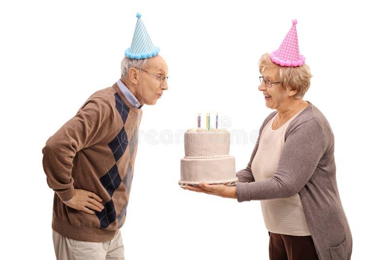 Van het de verjaardagscake en bejaarde van de bejaardeholding het blazen royalty-vrije stock afbeeldingen