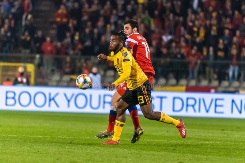Van het de voetbalteam van België de nationale striker Michy Batshuayi tegen de verdediger Georgi Dzhikiya van Rusland stock foto's