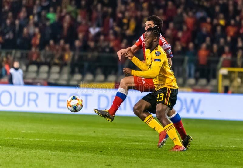 Van het de voetbalteam van België de nationale striker Michy Batshuayi tegen de verdediger Georgi Dzhikiya van Rusland stock afbeelding