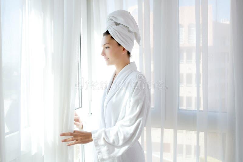 Van het de vrouwen de zonnige venster van de badjas witte gordijnen royalty-vrije stock foto