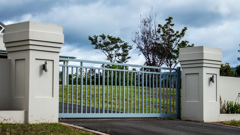 Van het de woonplaatsbezit van de metaaloprijlaan privé die de ingangspoorten in baksteenomheining worden geplaatst met tuinbomen royalty-vrije stock afbeelding
