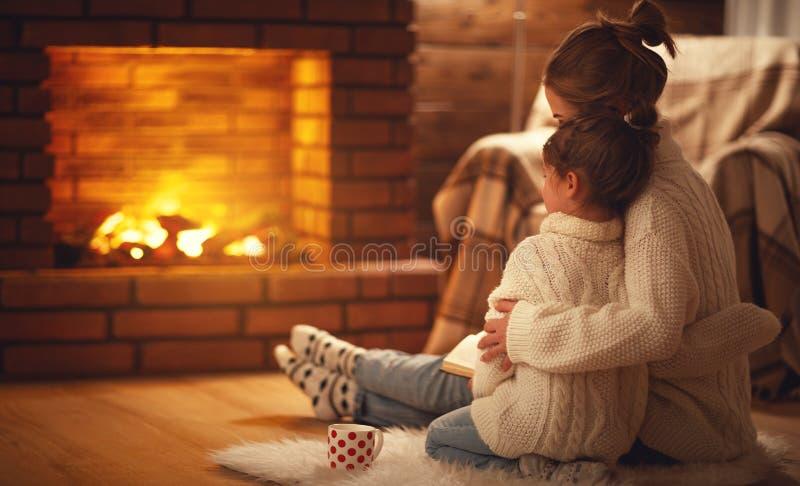 Van het familiemoeder en kind de omhelzingen en verwarmen op de winteravond door firep stock afbeeldingen