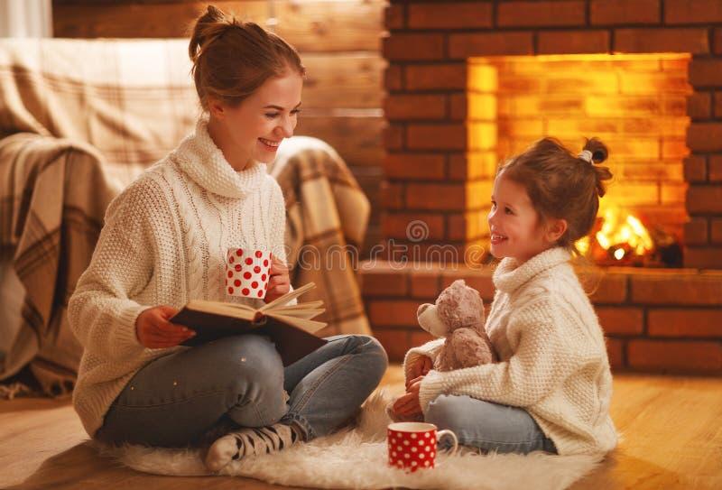Van het familiemoeder en kind lezingsboek op de winteravond door firepl royalty-vrije stock foto's