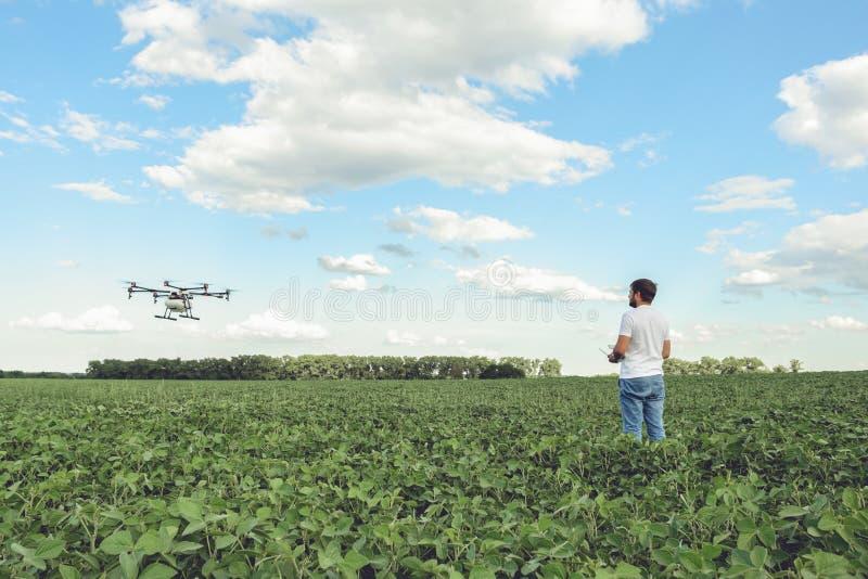 Van het gebruikswifi van de technicuslandbouwer van de de computercontrole de landbouwhommel op groen gebied royalty-vrije stock afbeelding